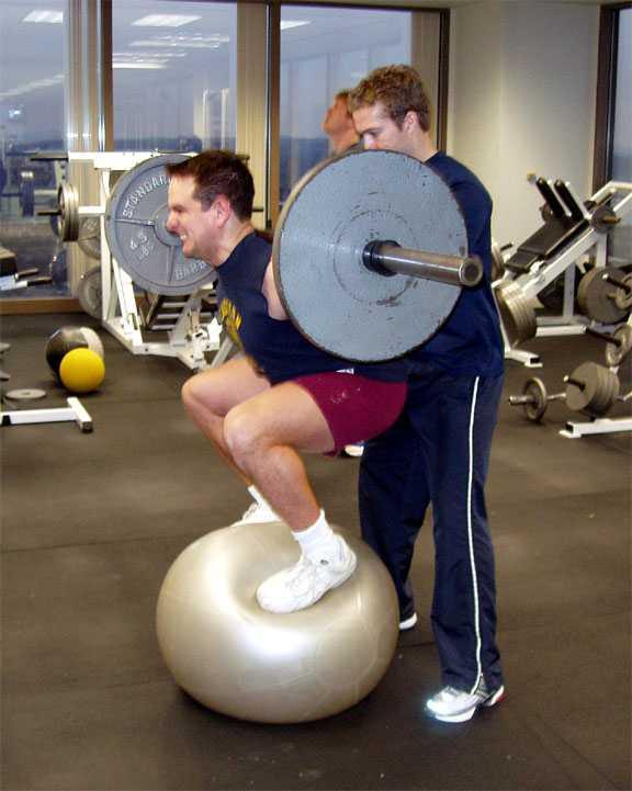 guy-on-ball-doing-squats - 33V Fitness